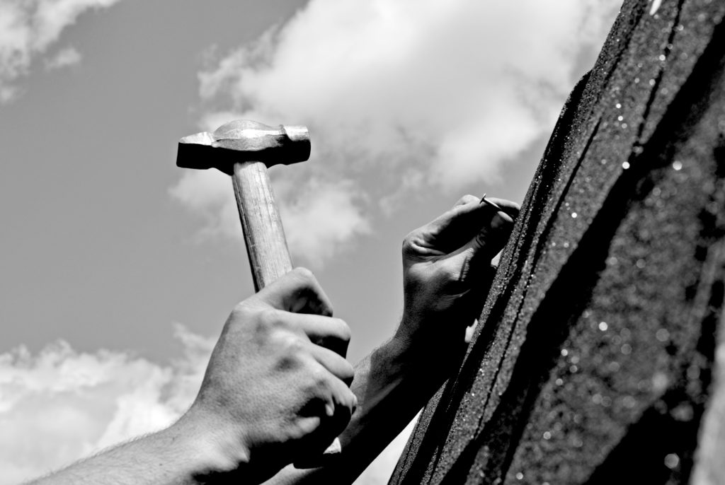 Black and white image of professional roofer hammering nails into shingles on a roof